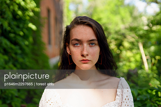 Young woman in the garden, portrait - p1646m2297665 by Slava Chistyakov