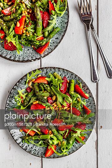Salad of green asparagus, rocket, strawberries and pine nuts - p300m1587328 von Sandra Roesch