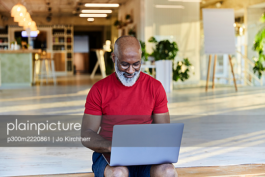 Mature man in red t-shirt using laptop while sitting at rooftop - p300m2220861 by Jo Kirchherr