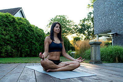 Woman practicing yoga in garden - p300m2060156 by harrylidy