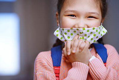 Girl with hands clasped wearing protective face mask during pandemic - p300m2273695 by Arman Zhenikeyev