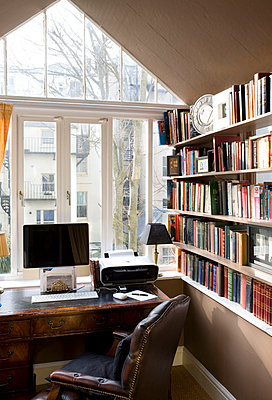 Desk with computer and chair at window with bookcase in  Hove home  East Sussex  UK - p3493413 by Robert Sanderson