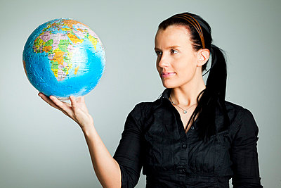 Woman standing with terrestrial globe in her hand - p4266830f by Tuomas Marttila