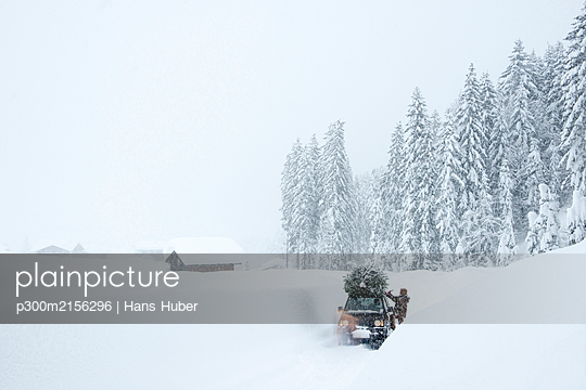 Austria, Salzburger Land, Lammertal, Man attaching Christmas tree to car roof on snowy road - p300m2156296 by Hans Huber