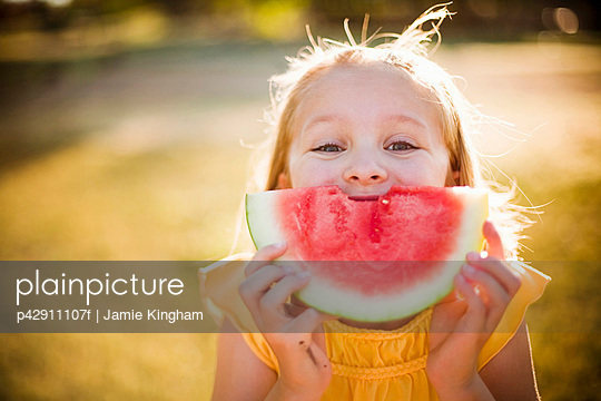 Young girl making smile with watermelon - p42911107f by Jamie Kingham