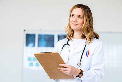 Smiling blond female doctor holding clipboard looking away - p300m2266155 by Giorgio Fochesato