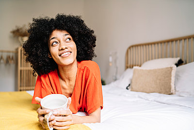 Thoughtful young woman with mug lying on bed at home - p300m2277203 by COROIMAGE