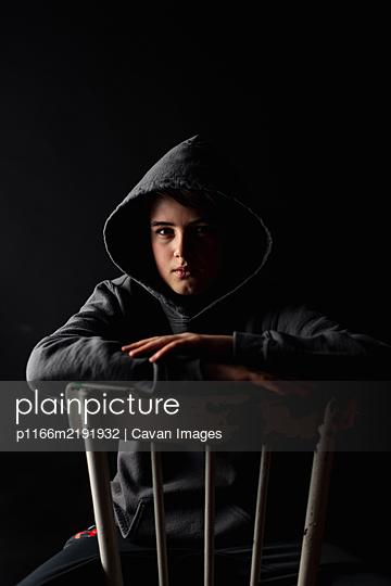 Portrait of adolescent boy in hoodie sitting on a chair in dark room. - p1166m2191932 by Cavan Images
