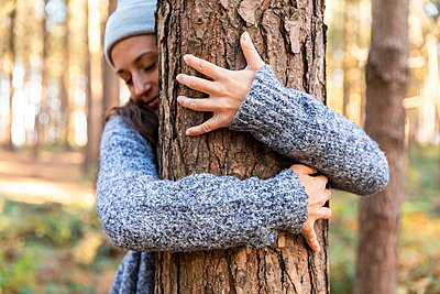 Female explorer embracing tree trunk while hiking in Cannock Chase woodland - p300m2241411 by William Perugini