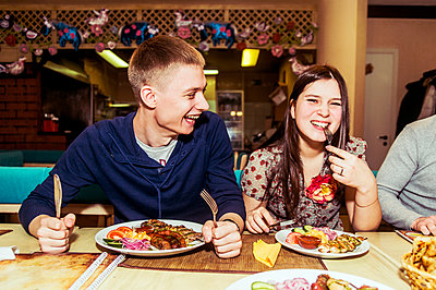 Caucasian couple laughing in restaurant - p555m1413184 by Aleksander Rubtsov