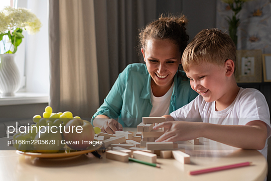 Happy mother and son playing on table - p1166m2205679 by Cavan Images