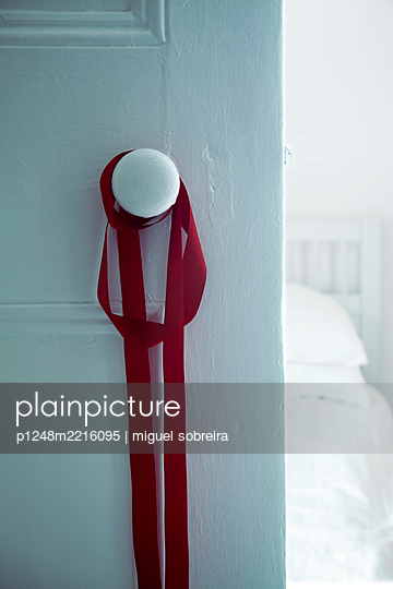 Red Ribbon Wrapped Around Bedroom Doorknob  - p1248m2216095 by miguel sobreira