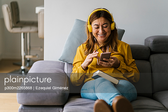 Smiling woman with headphones using smart phone while sitting on sofa in living room - p300m2265868 by Ezequiel Giménez