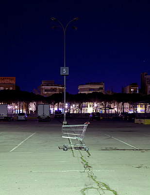 Shopping trolley abandoned in a car park outside a shopping mall at night in Barcelona - p1072m829072 by Joan Seculi