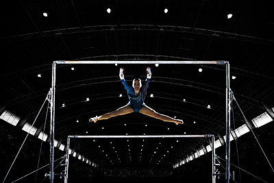 A female gymnast, a young woman performing on the parallel bars performing, with legs extended. - p1100m1095655 by Mint Images