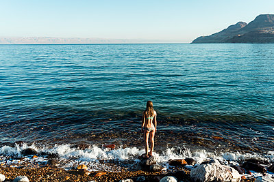 Rear view of woman looking at sea while standing on rock - p1166m1174113 by Cavan Images