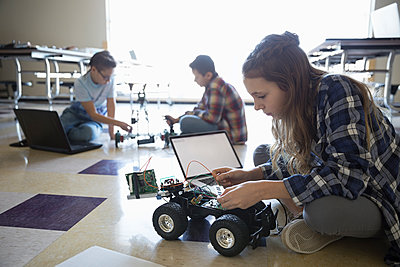Pre-adolescent girl programming robotics at laptop on classroom floor - p1192m1231005 by Hero Images