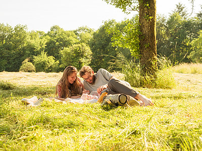 Young couple relaxing with baby girl on blanket in nature - p300m2070254 by Albrecht Weißer