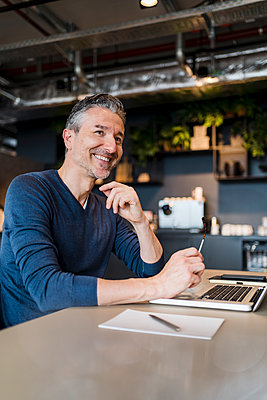 Smiling mature businessman with laptop sitting at desk in creative office while looking away - p300m2287425 by Daniel Ingold