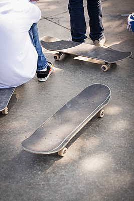 Boys with skateboards on pavement - p301m2296794 by Peter Stark
