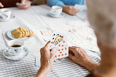 Cropped image of senior woman playing cards with family at table - p426m1468275 by Maskot