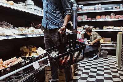 Midsection of male customer holding shopping basket at delicatessen shop - p426m2270529 by Maskot