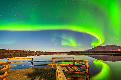 The Northern Lights are seen reflecting off Beach Lake on a clear, autumn night with a wooden dock in the foreground; Chugiak, Alaska, United States of America - p442m2091868 by Michael Jones