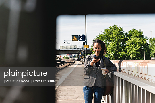 Young woman at train station reading text messages on her phone - p300m2004581 von Uwe Umstätter