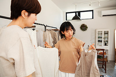 Two Japanese women standing in a small fashion boutique, looking at tops. - p1100m2146458 by Mint Images