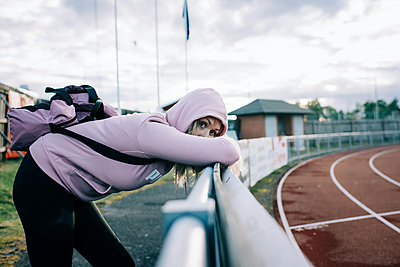 woman looking nervous stood by a running track waiting - p1166m2208435 by Cavan Images