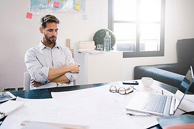 Portrait of pensive architect sitting at desk - p300m1499451 by Giorgio Fochesato