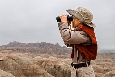 boy wearing explorer costume holding binoculars,  - p343m1446670 by Steve Glass