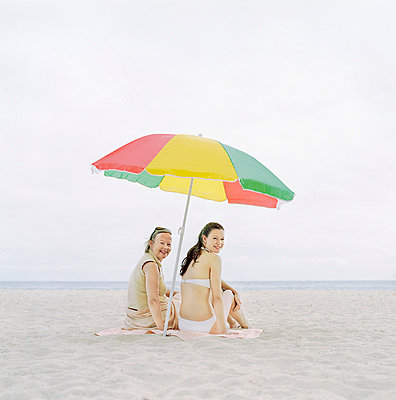 Rear view of a mature woman sitting with her daughter on the beach - p3741549 by Karin Smeds