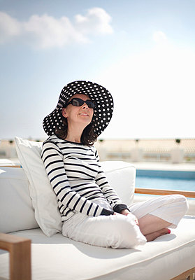 Woman relaxing in sunshine - p42912257f by Ashley Jouhar