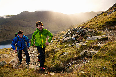 Men hiking on rocky mountainside - p42914157f by Ross Woodhall