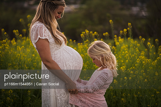 Pregnant mother with daughter standing in park during sunset - p1166m1544951 by Cavan Social