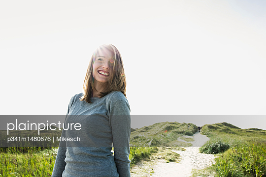 Happy young woman on St. Peter Ording beach  - p341m1480676 by Mikesch