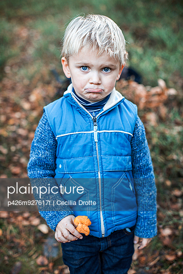 Portrait of sad young boy holding mushrooms in forest