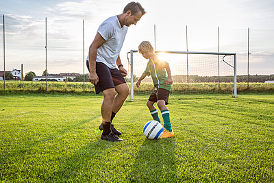 Coach and young football player on football ground at sunset - p300m1581381 by Fotoagentur WESTEND61