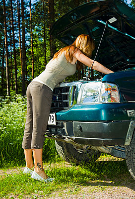 Woman fixing car - p4265599f by Tuomas Marttila