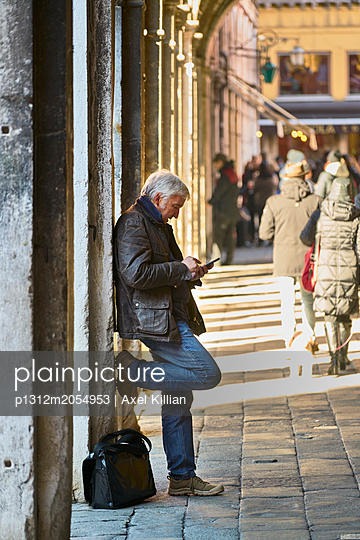 Mann mit Smartphone lehnt an einer Wand - p1312m2054953 von Axel Killian