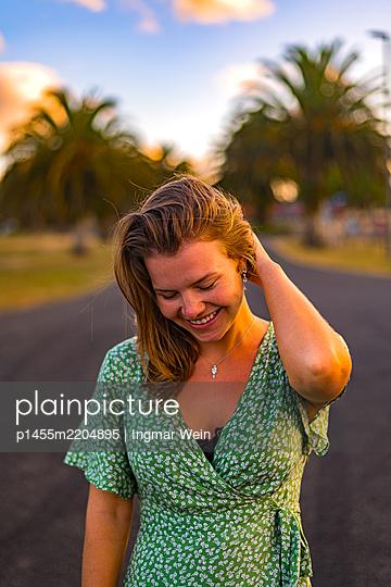 Happy woman in green summer dress - p1455m2204895 by Ingmar Wein