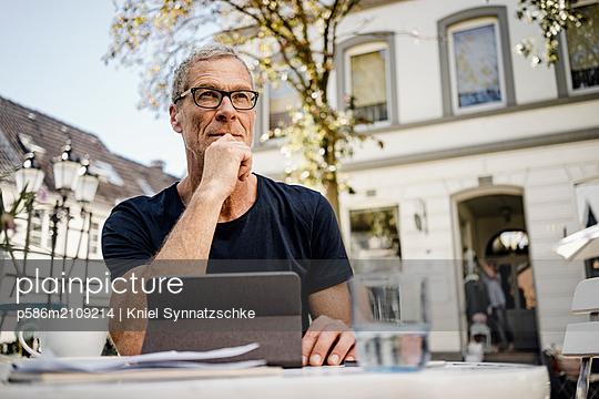 Senior sitzt mit Laptop im Straßencafe - p586m2109214 von Kniel Synnatzschke