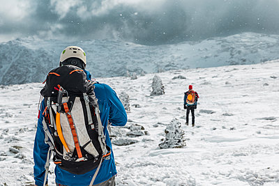 Rear view of backpackers standing on snowy landscape during storm at White Mountains - p1166m1566942 by Cavan Images