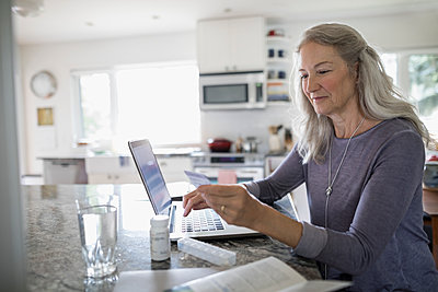 Senior woman with credit card reordering prescription medication at laptop in kitchen - p1192m1529638 by Hero Images