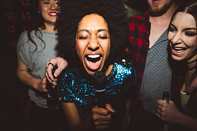 Exuberant young female millennial singing karaoke - p1192m1567130 by Hero Images