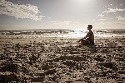 Mann meditiert auf dem Strand in der Abendsonne - p1640m2261019 von Holly & John