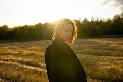 Young woman in stubble field in the evening sun - p1646m2249824 by Slava Chistyakov