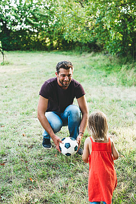 Happy father playing football with daughter on meadow - p300m2058830 by Epiximages