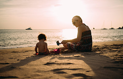 Thailand, Koh Lanta, mother playing with little daughter on the beach by sunset - p300m2069833 von Gemma Ferrando